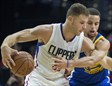 Blake Griffin bota el balón ante la defensa de Stephen Curry